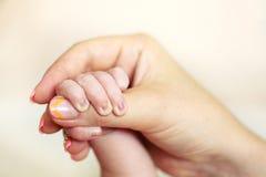 在mom& x27的婴孩手; s手有被弄脏的背景 免版税图库摄影