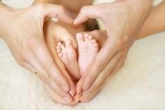 在mom& x27的婴孩脚; s和dad& x27; s手有被弄脏的背景 库存图片