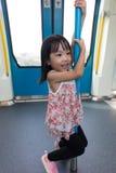 在MRT运输里面的亚洲中国小女孩杆跳舞 库存照片