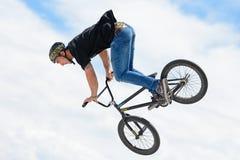 在MTB (骑自行车的山)竞争的一个专业车手在泥铺跑道 库存照片