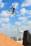 在MTB (骑自行车的山)竞争的一个专业车手在泥铺跑道 库存图片
