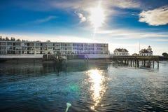 在Mukilteo轮渡码头排行江边的住所,当小船离去到惠德比岛在一个冷的冬天早晨 免版税库存图片