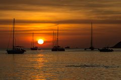 在Nai哈恩海滩的令人惊讶的红色日落在普吉岛 免版税库存图片