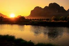 在Nam歌曲河的日落有在V的现出轮廓的岩层的 免版税库存照片