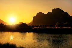 在Nam歌曲河的日落有在V的现出轮廓的岩层的 免版税图库摄影