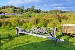 在New Zealand湖的边缘的一辆小船拖车 免版税库存照片