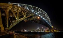 在nihgt的悉尼港桥的东边与明亮反射在港口中被弄脏的水域  库存照片