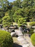 在Nijo-jo城堡池塘的石桥梁 免版税图库摄影