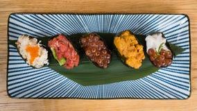 在nori海草、不同的大小金枪鱼鞑靼,鱼子酱和颜色鲕梨包裹的不同的品种gunkan,海 免版税库存照片