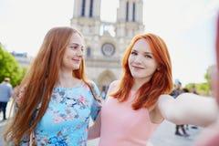 在Notre Dame附近的两个女孩在巴黎 库存图片