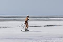 在Ob水库的冻冰的滑雪者赤裸上身的奔跑 免版税图库摄影
