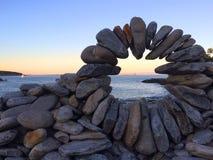 在oceanview日落旁边的特别岩石安排 免版税库存图片