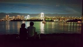 在Odaiba的公开海滩有彩虹视图夜 库存照片