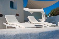 在Oia大阳台的两把longue椅子圣托里尼的,希腊 图库摄影