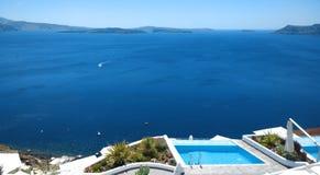 在Oia镇在海和原始水池的惊人的看法在峭壁边缘有一个惊人的看法 库存照片