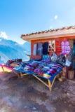 在Ollantaytambo,秘鲁,南美街道上的纪念品市场。五颜六色的毯子,盖帽,围巾,布料,雨披 免版税图库摄影