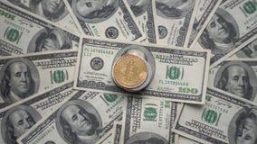 在othe上面的金子Bitcoin铸造转动在100美元票据  全世界真正互联网cryptocurrency和 股票录像