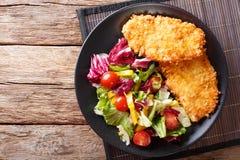 在Panko和新鲜的沙拉特写镜头上添面包的鸡牛排在 免版税库存照片