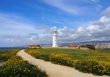 在paphos与春天的历史建筑之前包围的塞浦路斯的老灯塔沿着导致海的道路开花 免版税库存图片