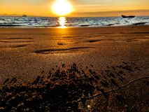 在Pebble海滩的美好的日出有沙子和脚步的 库存图片