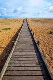 在Pebble海滩的长的平直的木路 免版税库存图片
