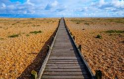在Pebble海滩的长的平直的木路 库存图片