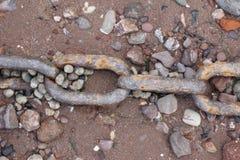 在Pebble海滩的生锈的链子 免版税库存照片