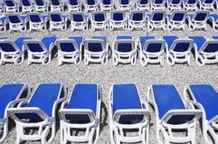 在Pebble海滩的蓝色sunbeds 库存图片