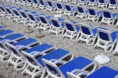 在Pebble海滩的蓝色sunbeds 免版税库存图片