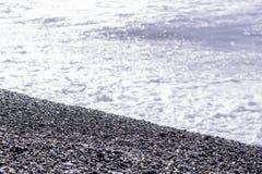 在Pebble海滩背景的蓝色波浪海浪 图库摄影