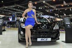 在Peugeot RCZ旁边的泰国女性赠送者 免版税库存照片