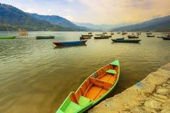 在phewa湖日落的客船停车处在背景 博克拉尼泊尔 免版税库存照片