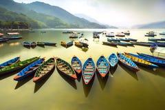 在Phewa湖的令人惊讶的看法 在排队的五颜六色的小船在午间 免版税库存图片