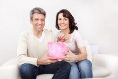 在piggybank的成熟夫妇节省额货币 免版税库存照片