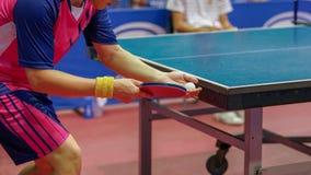 在pingpon比赛期间,一个桃红色衬衣人服务一个球 免版税库存图片