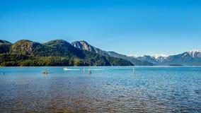 在Pitt湖的渔船有金黄耳朵的雪加盖的峰顶,兴奋峰顶和海岸山脉其他山峰的  库存照片