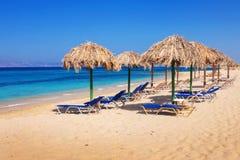 在Plaka海滩,纳克索斯岛的Sunbeds 免版税图库摄影