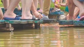 在planked人行道的游人脚在湖递哺养的鱼 股票录像