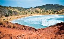 在Playa de Cavalleria, Menorca的红色岩石 免版税库存图片