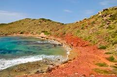 在Playa de Cavalleria, Menorca的红色岩石 免版税图库摄影