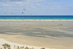 在Playa de Sotavento的人风帆冲浪& Kitesurfing在费埃特文图拉岛 库存图片