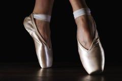 在pointes的特写镜头经典芭蕾舞女演员` s腿在黑地板上 库存图片