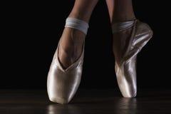 在pointes的特写镜头经典芭蕾舞女演员` s腿在黑地板上 免版税库存图片