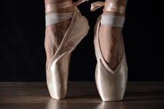 在pointes的特写镜头经典芭蕾舞女演员` s腿在黑背景和木灰色地板 免版税图库摄影
