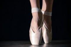 在pointes的特写镜头经典芭蕾舞女演员` s腿在黑背景和木灰色地板 免版税库存照片