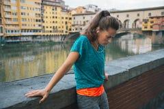在ponte vecchio前面的疲乏的健身妇女在佛罗伦萨,意大利 免版税库存图片