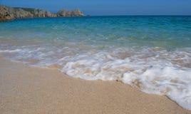 在porthcurno沙滩的发泡的波浪,凯尔特海,夏天在康沃尔郡,南伦敦西区,英国纯净的水  免版税库存照片