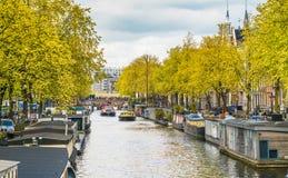在Prinsengracht运河的地方和旅游航行在春天在Jordaan地区与小船、自行车和汽车 免版税库存图片