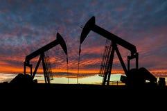 在Pumpjack剪影的剧烈的天空在农村亚伯大,加拿大 免版税图库摄影
