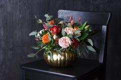 在punpkin花瓶的秋天百花香在黑椅子 库存照片